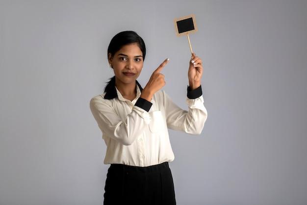 Jonge vrouw of bedrijfsvrouw die een klein knipselraad in haar handen op een grijze muur houden.
