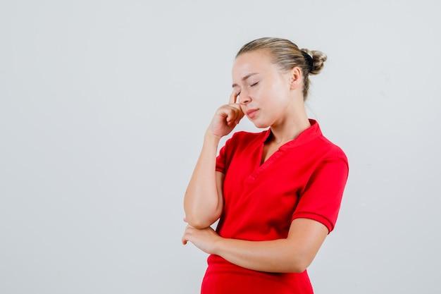 Jonge vrouw ogen in rood t-shirt sluiten en peinzend kijken