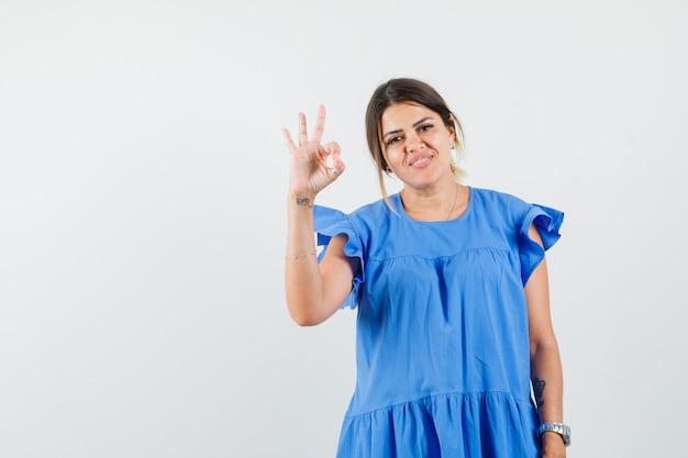 Jonge vrouw ok gebaar in blauwe jurk tonen en vrolijk kijken