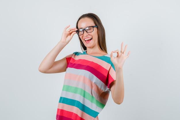 Jonge vrouw ok gebaar met vingers op bril in t-shirt tonen en vrolijk kijken. vooraanzicht.