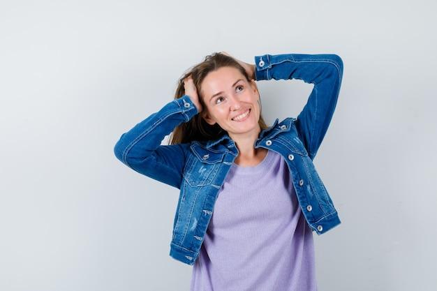 Jonge vrouw omklemd hoofd met handen, opzoeken in t-shirt, jas en er gelukkig uitzien. vooraanzicht.