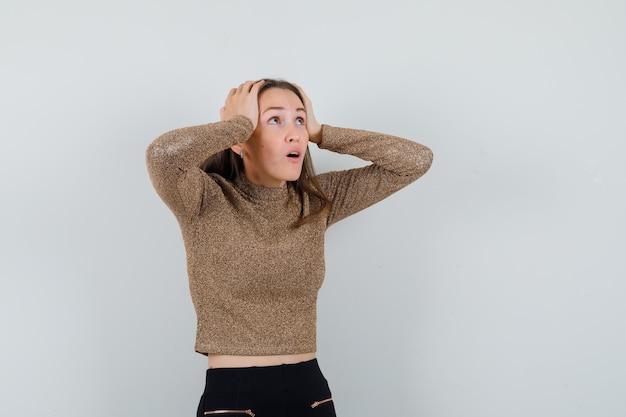 Jonge vrouw omklemde hoofd met handen in gouden blouse en op zoek verontrust