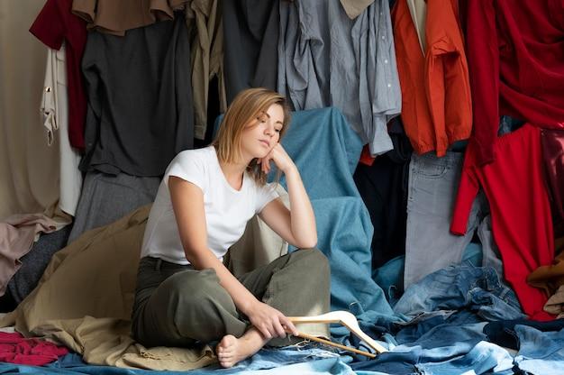 Jonge vrouw omringd door stapels kleren