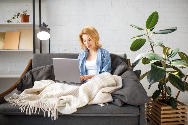 Jonge vrouw onder een deken met laptop op gezellige gele bank, woonkamer in witte tinten