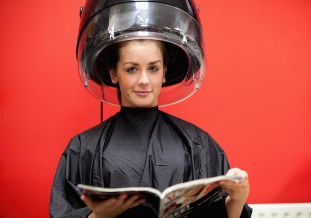 Jonge vrouw onder een kapper machine
