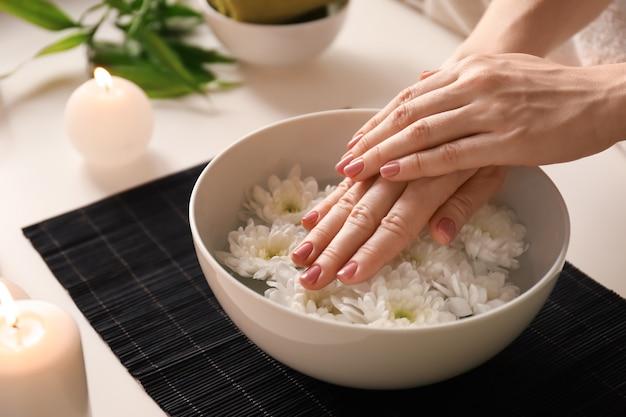 Jonge vrouw ondergaat spa manicure behandeling in schoonheidssalon, close-up,