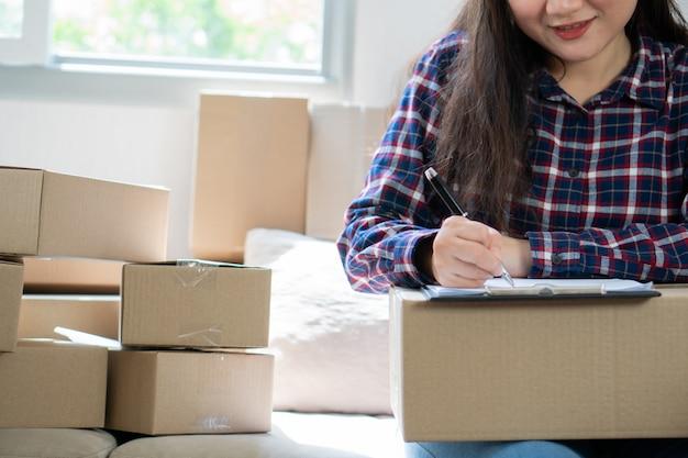 Jonge vrouw ondernemer, zittend op de bank en thuis werken. jaarlijkse omzet opnemen