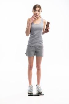 Jonge vrouw ongelukkig met haar gewicht met chocolade, geïsoleerd op wit.