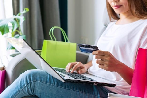 Jonge vrouw online winkelen en betaling met een creditcard thuis