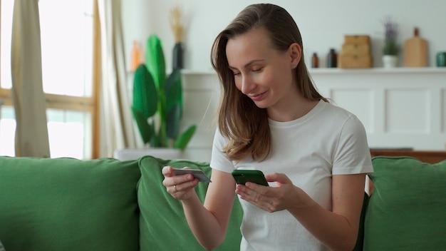 Jonge vrouw online winkelen met creditcard en smartphone zittend op de bank thuis.