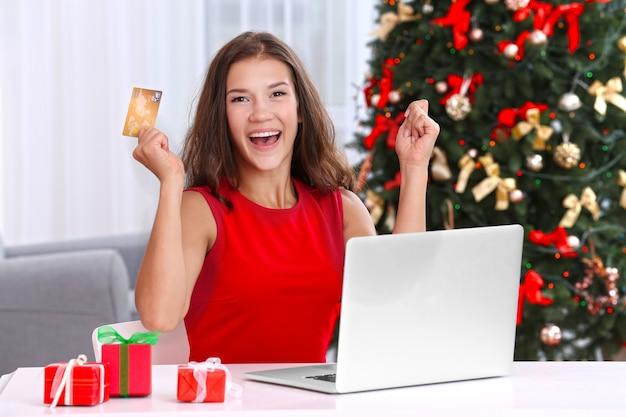 Jonge vrouw online winkelen met creditcard thuis voor kerstmis