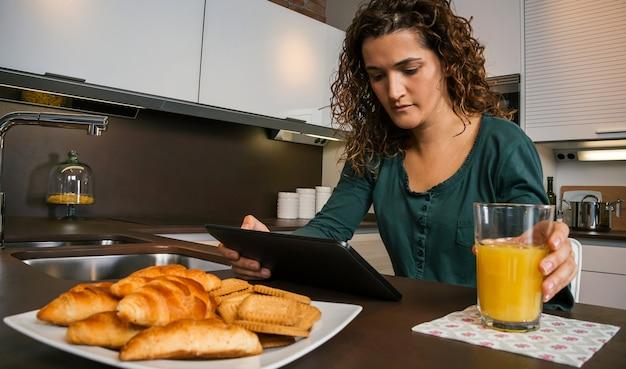 Jonge vrouw ontbijten in de keuken en kijken naar de tablet