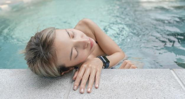 Jonge vrouw ontspannen bij het zwembad in de zomer.