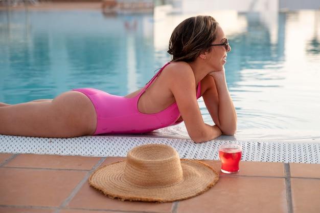 Jonge vrouw ontspannen bij het zwembad