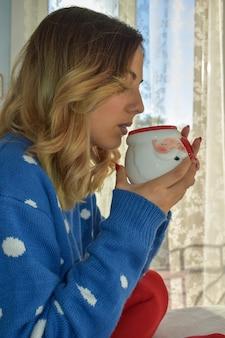 Jonge vrouw ontspannen en drinken 's ochtends koffie thuis