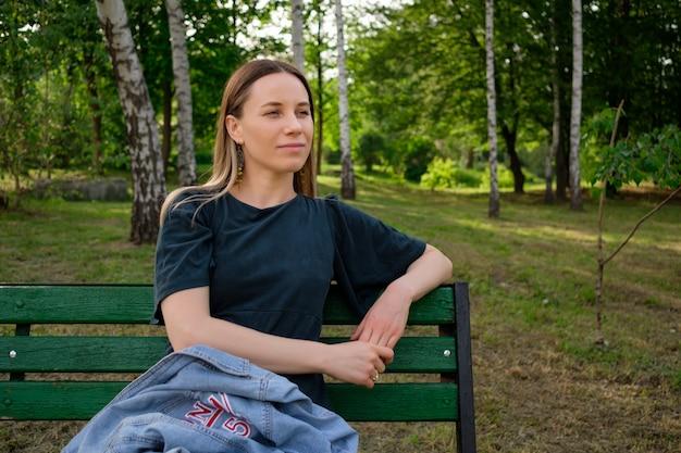 Jonge vrouw ontspannen in het park zittend op een stoel