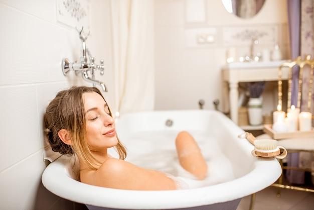 Jonge vrouw ontspannen in het prachtige vintage bad vol schuim in de retro badkamer versierd met kaarsen