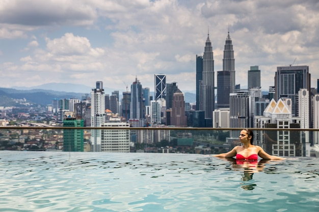 Jonge vrouw ontspannen in het zwembad op een warme dag