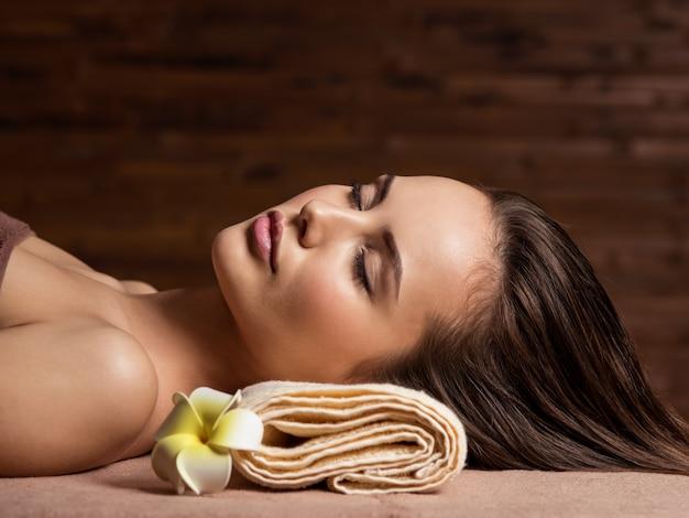 Jonge vrouw ontspannen in spa salon. schoonheidsbehandeling. spa salon