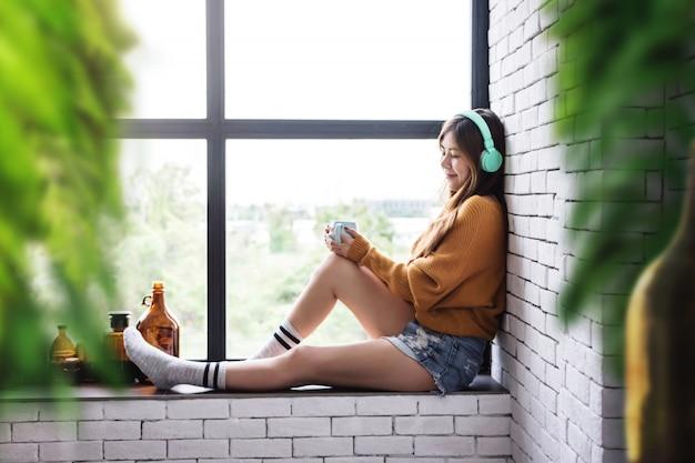 Jonge vrouw ontspannen met muziek van hoofdtelefoon in gezellige huis nabijgelegen venster, genieten met morning sunshine en warme koffie