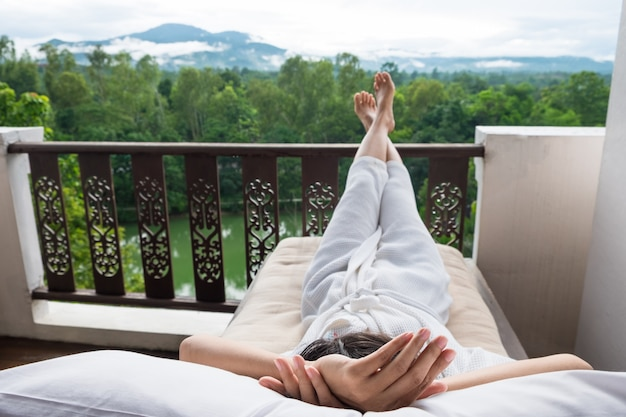 Jonge vrouw ontspannen op bed en geniet van uitzicht op de bergen