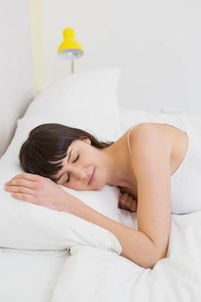 Jonge vrouw ontspannen op bed in de slaapkamer
