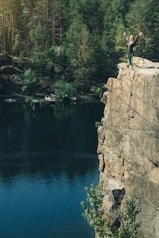 Jonge vrouw ontspannen op de klif van het eiland, kijkend naar het diepblauwe water
