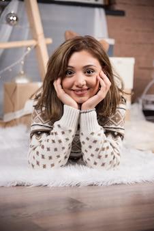 Jonge vrouw ontspannen op de woonkamer in kerst versierd huis