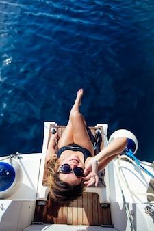 Jonge vrouw ontspannen op het jacht op zee op zonnige dag