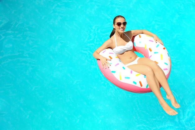 Jonge vrouw ontspannen op opblaasbare donut in zwembad