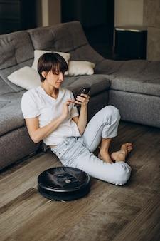 Jonge vrouw ontspannen terwijl robot de vloer stofzuigt