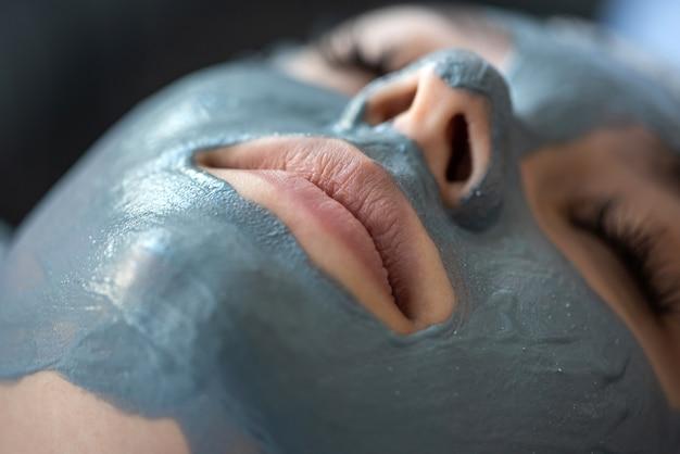 Jonge vrouw ontspant in een beauty spa na het aanbrengen van een masker op haar gezicht. zorgconcept