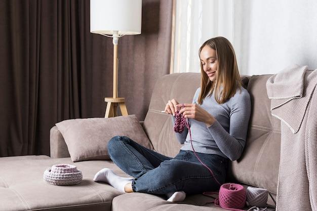 Jonge vrouw ontspant 's avonds thuis, breit zittend op een bank.