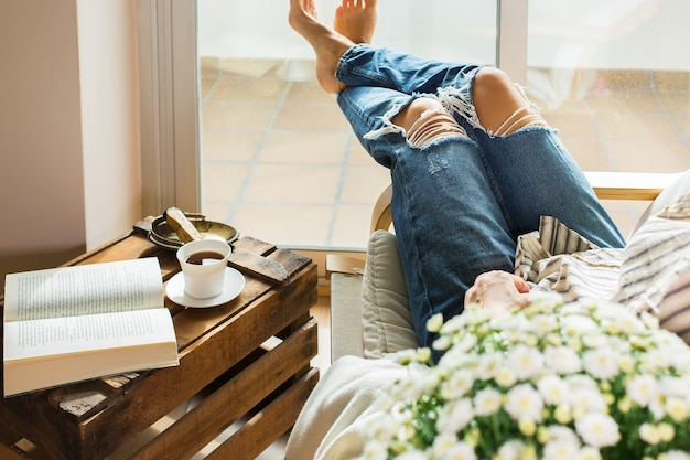 Jonge vrouw ontspant thuis en drinkt thee leesboek
