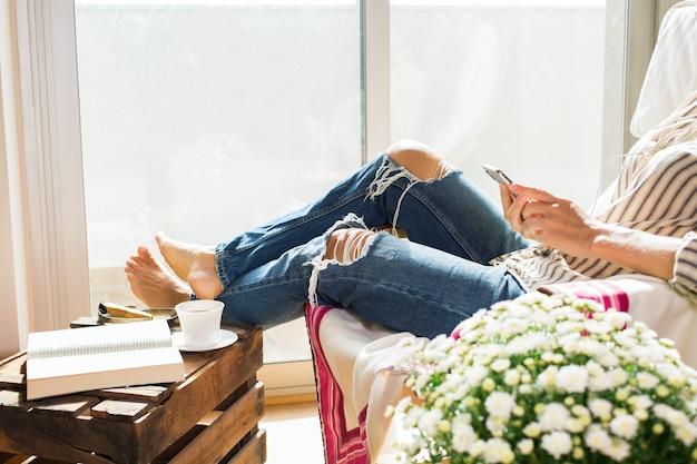 Jonge vrouw ontspant thuis en drinkt thee met de telefoon