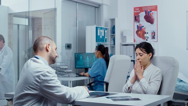 Jonge vrouw ontvangt verwoestend nieuws van de dokter over haar gezondheid, ze begint te huilen en voelt zich verloren, verdrietig, depressief. kanker of ander terminaal ziek concept