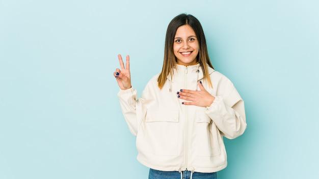 Jonge vrouw op blauwe muur die een eed afleggen, die hand op borst zetten.