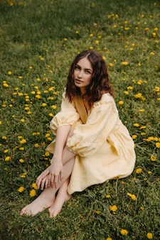 Jonge vrouw op blote voeten, gekleed in een gele jurk, zittend in een veld met paardebloemen