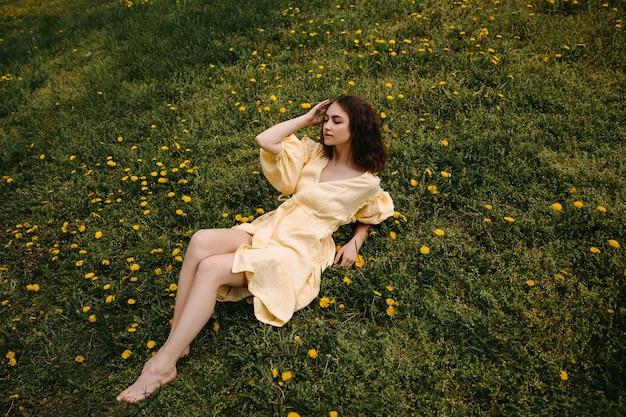 Jonge vrouw op blote voeten in een gele jurk ontspannen in een veld met groen gras en paardebloemen