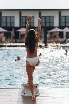 Jonge vrouw op de achtergrond van het zwembad in een wit zwempak