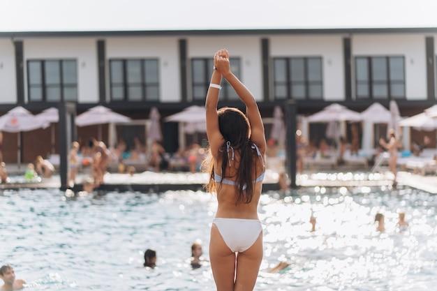 Jonge vrouw op de achtergrond van het zwembad in een witte zwembroek