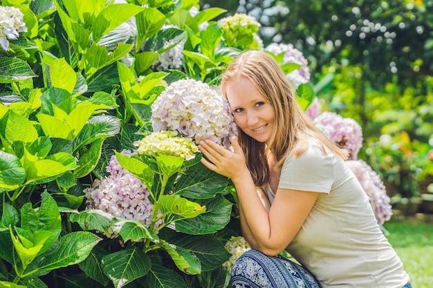 Jonge vrouw op de achtergrond van licht roze hortensia bloeien in de tuin