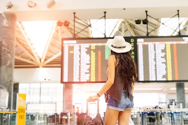 Jonge vrouw op de internationale luchthaven die naar het vluchtinformatiebord kijkt en haar vlucht controleert. vertrek- en aankomstbord. onherkenbare rug