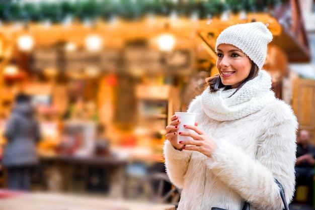 Jonge vrouw op de kerstmarkt