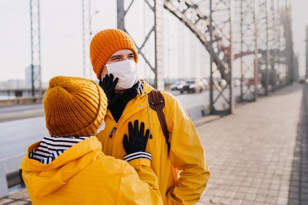 Jonge vrouw op de lege brug die voor haar vriend zorgt en zijn chirurgische gezichtsmasker controleert dat hij opzette vanwege het coronavirus. covid-19 pandemisch concept.