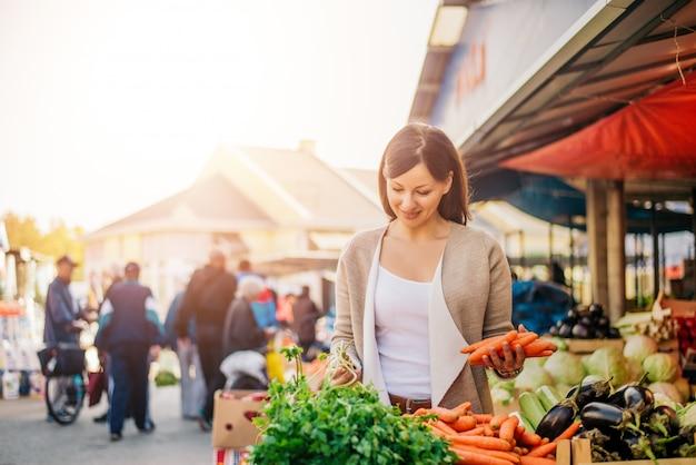 Jonge vrouw op de markt die groenten kopen.