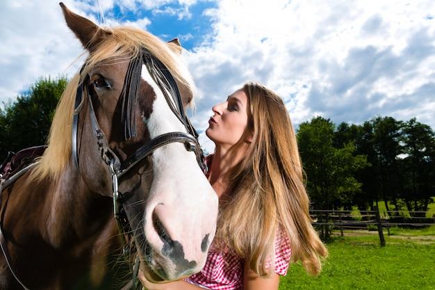 Jonge vrouw op de weide met paard en kussen