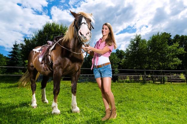 Jonge vrouw op de weide met paard