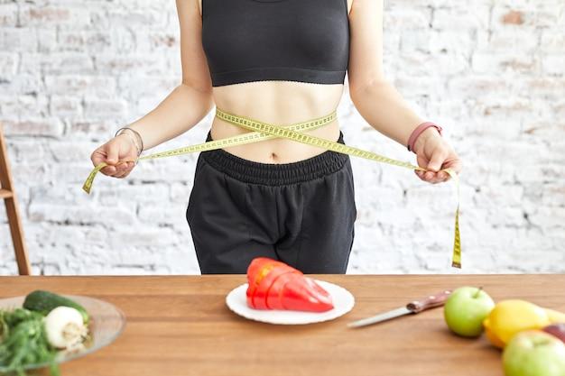 Jonge vrouw op dieet, ze meet haar taille met een zacht meetlint, verse groenten op tafel