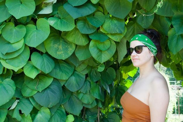 Jonge vrouw op een achtergrond van een zomer groen park, groene bladeren. een meisje met zwart haar, een groen verband op zijn hoofd, een bruine tanktop en een zwarte zonnebril.